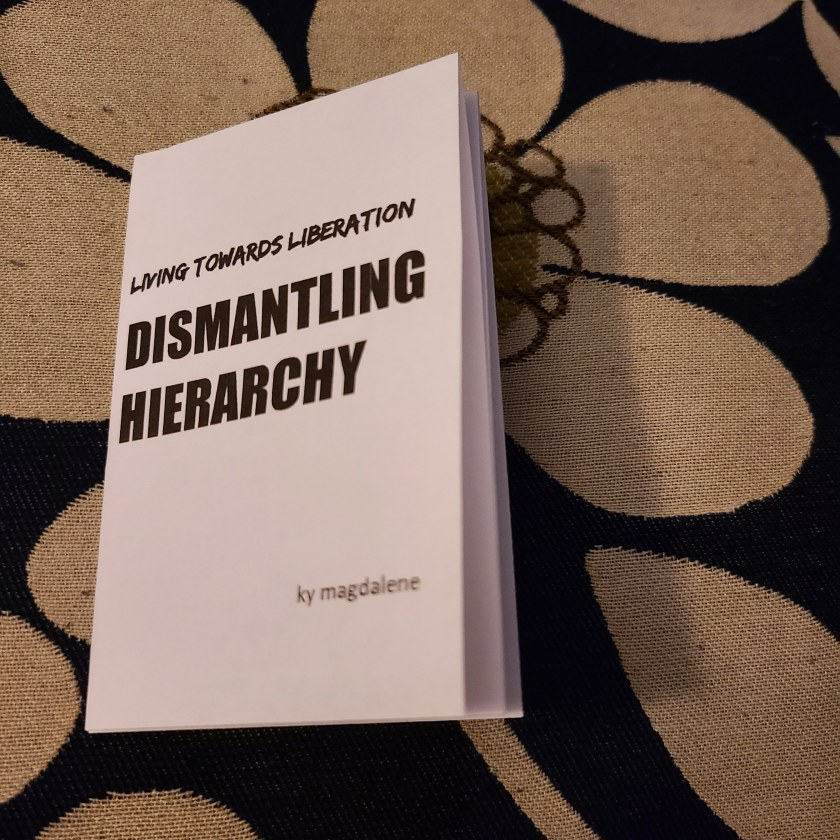 "image description: an eight-page mini zine titled ""living towards liberation: dismantling hierarchy"" placed against a backdrop with a large floral pattern. the cover of the zine also notes ky magdalene as the author."